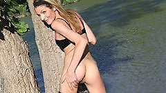 Fuckable Lola showing a little tit and ass by the lake.