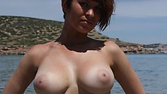 Short Haired girl with huge boobs flaunts it on the beach.